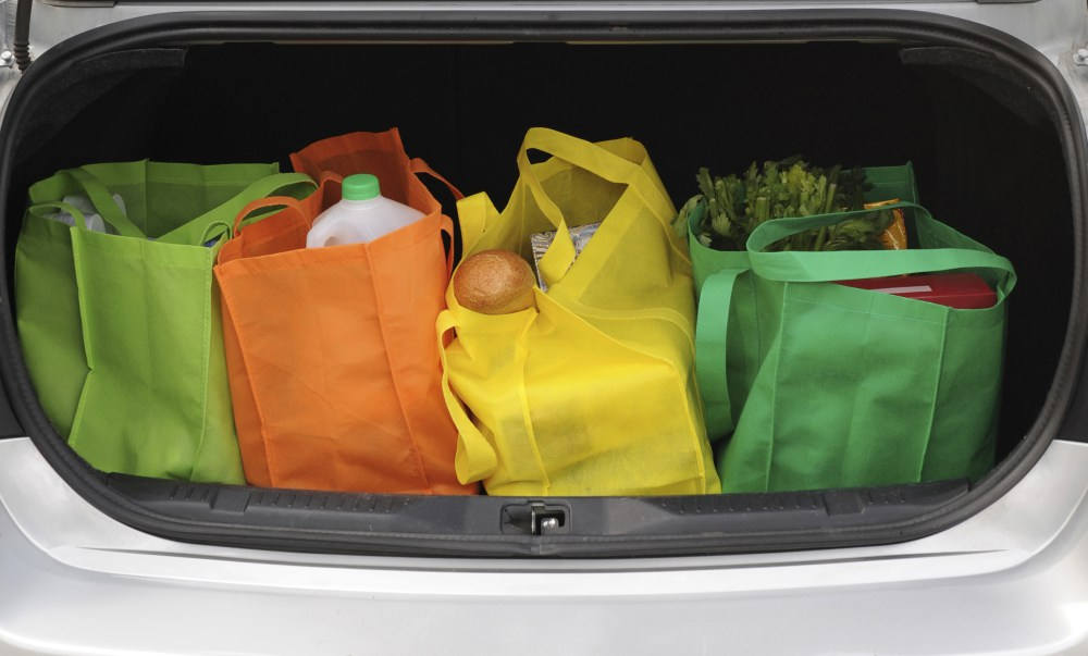Four colorful eco-friendly shopping bags filled mostly with groceries in the opened trunk of a car.