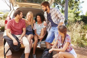 Group Of Friends On Trip Sitting In Trunk Of Car