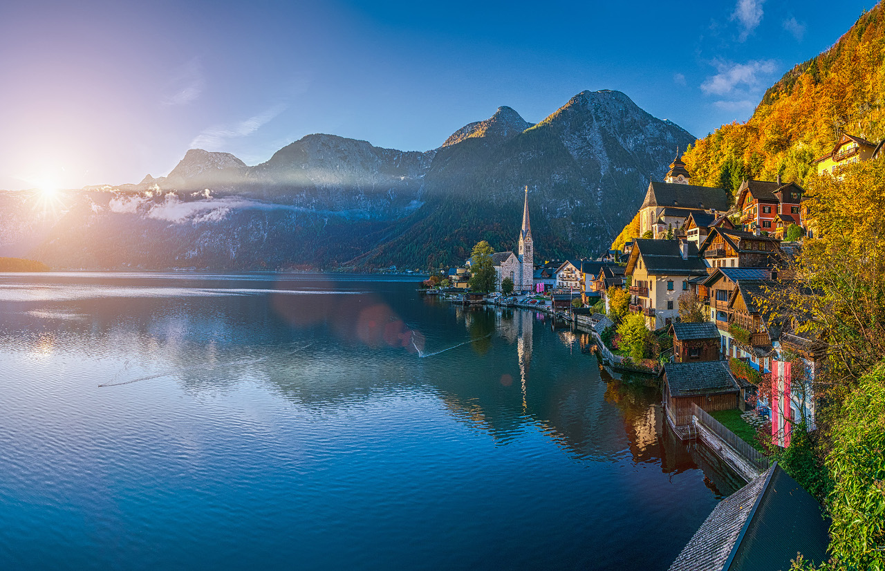 Hallstatt mountain village in fall, Salzkammergut, Austria. Hallstatt is one of the best cities to visit in Europe in autumn. If you like colorful autumn trees, then read this article and discover where to see the most beautiful fall colors in Europe #Europe #fall #fallfoliage #foliage #europefoliage #fallcolors #fallcolours #colours#autumn #austria